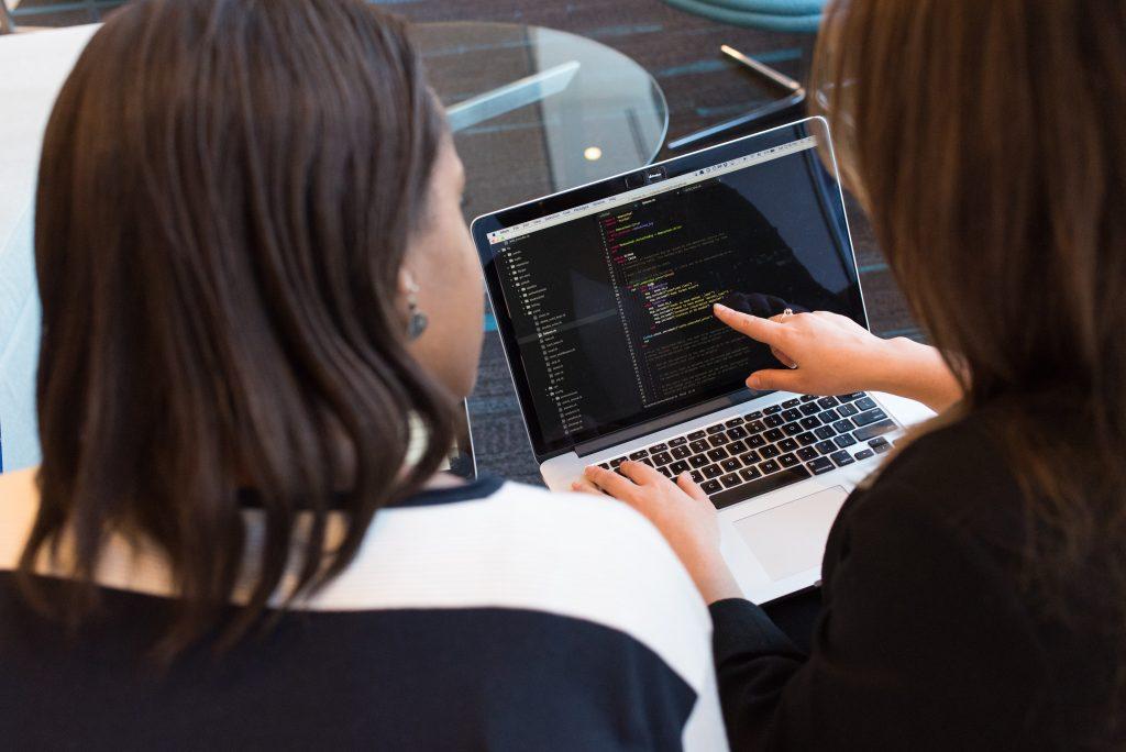 women analysing code on laptop