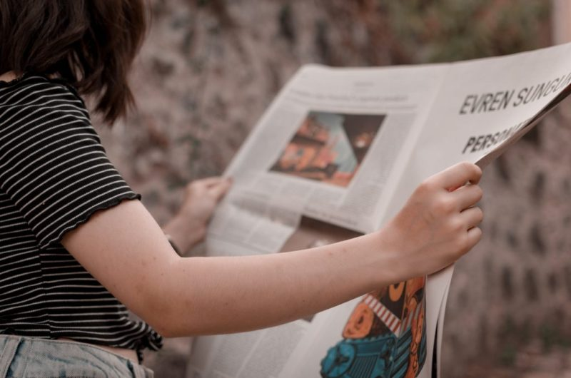 person reading newspaper with text and illustrations