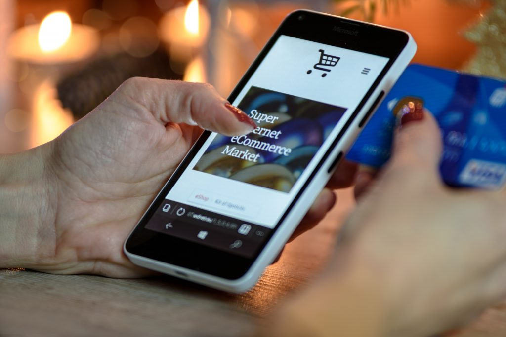 hand holding phone showing e-commerce business website