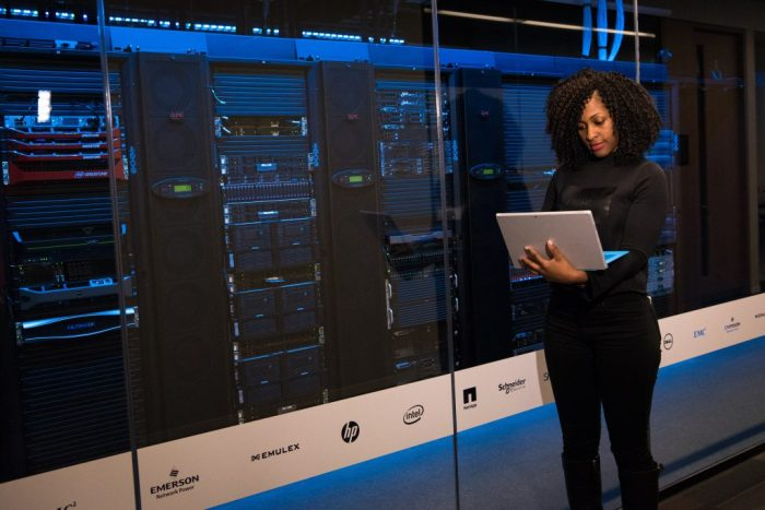 woman holding laptop in front of server for data protection