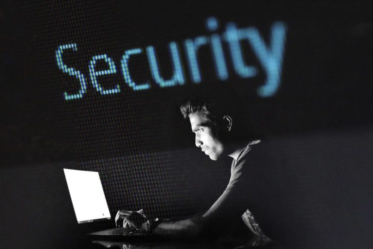 person in front of laptop typing to prevent website threats