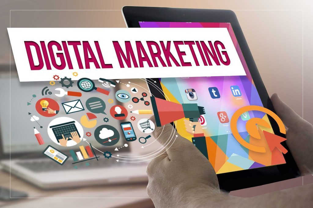 hands holding tablet with digital marketing words and icons