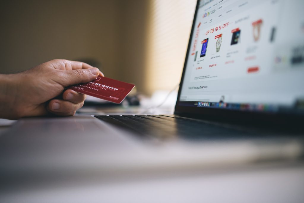 hand holding credit card in front of small business website for ecommerce