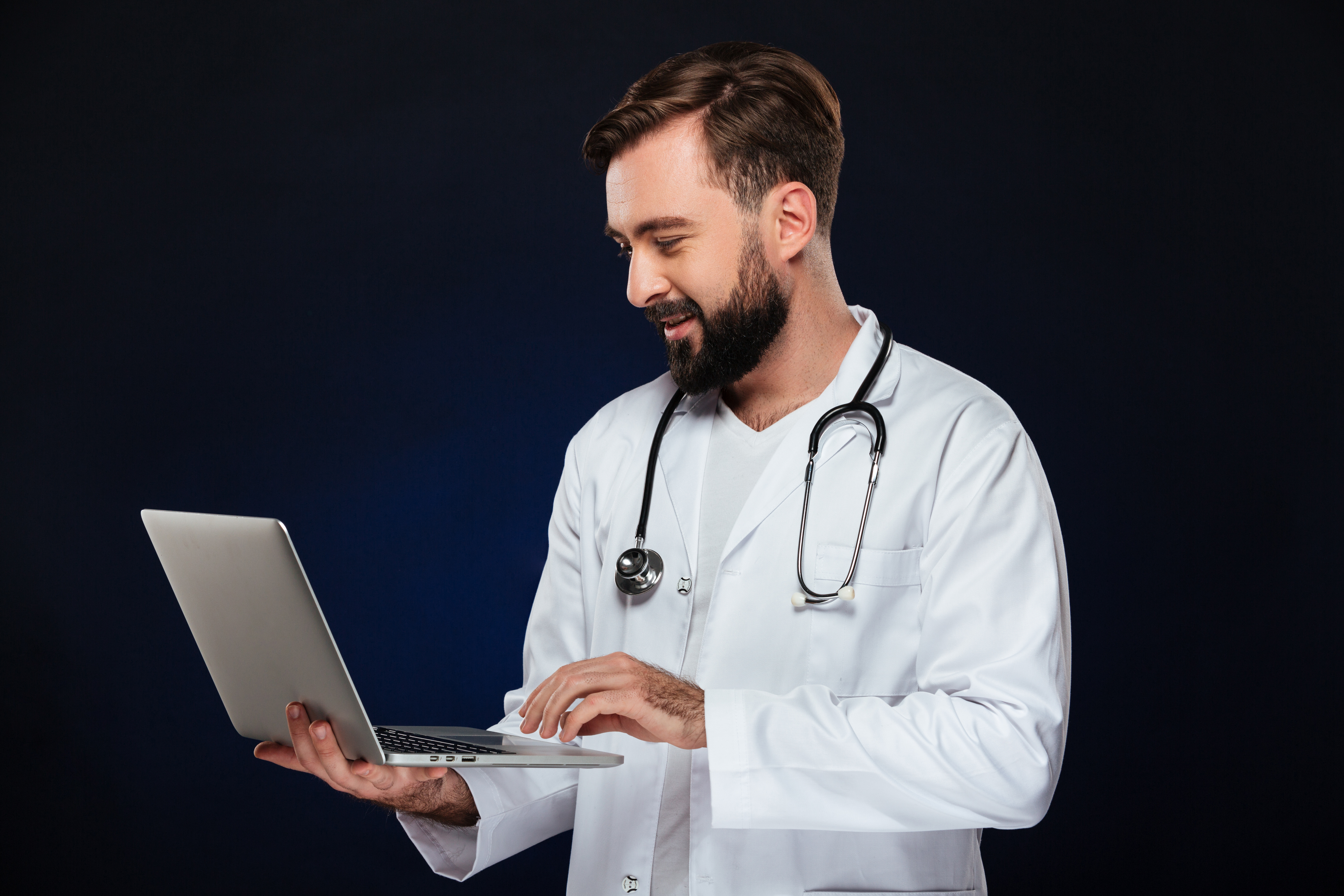 doctor in uniform holding laptop for pxtrack patient tracking system initial setup