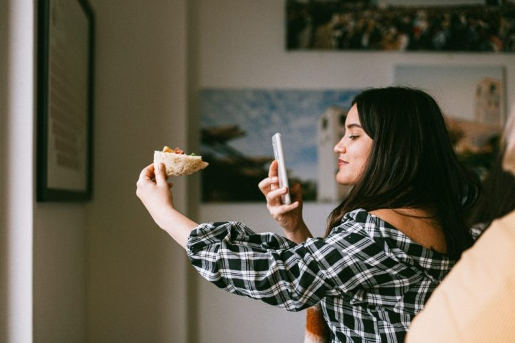 girl taking picture of food for instagram marketing prediction that user generated content is prominent