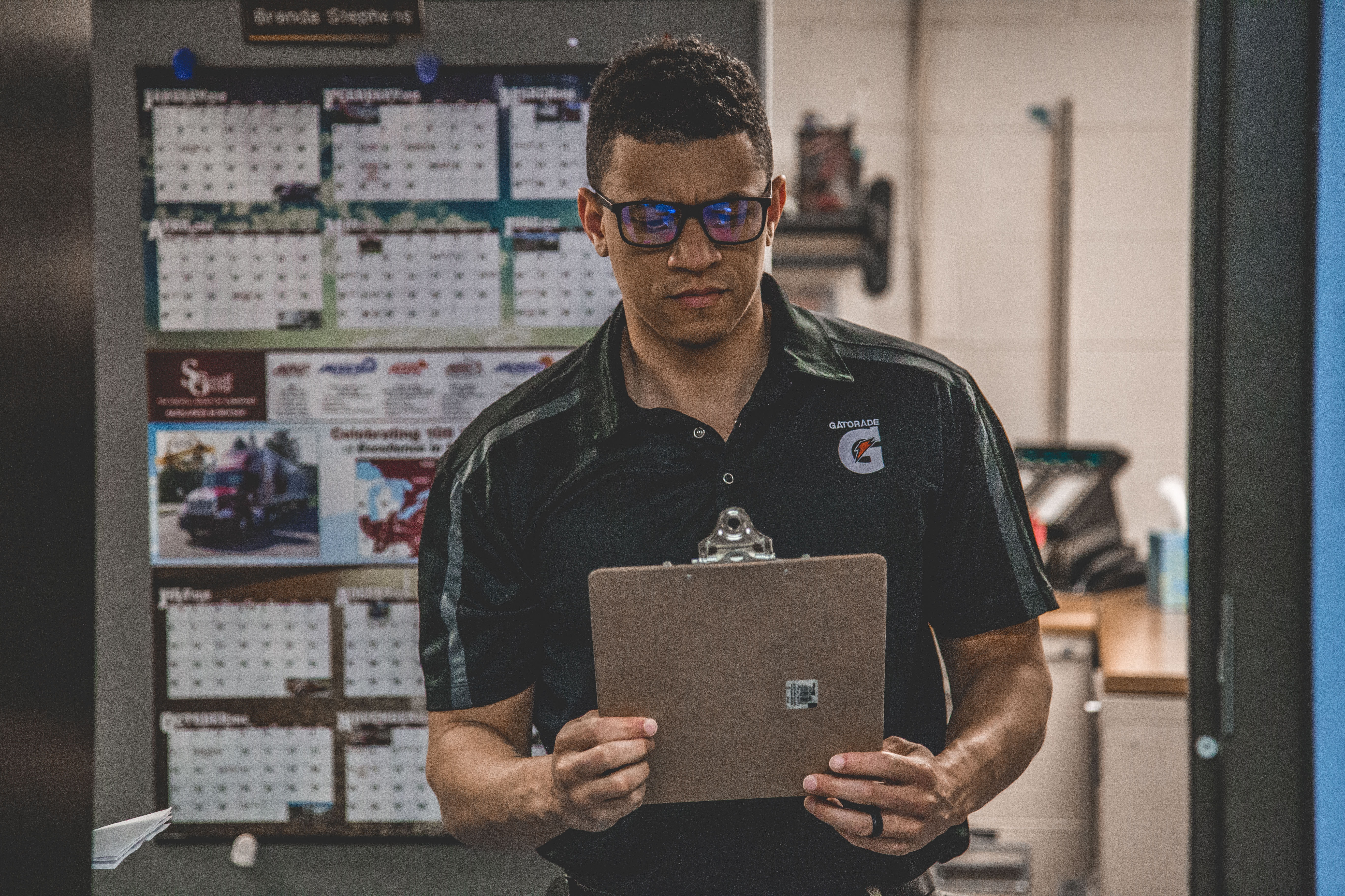 man with glasses holding clipboard to check inventory stock