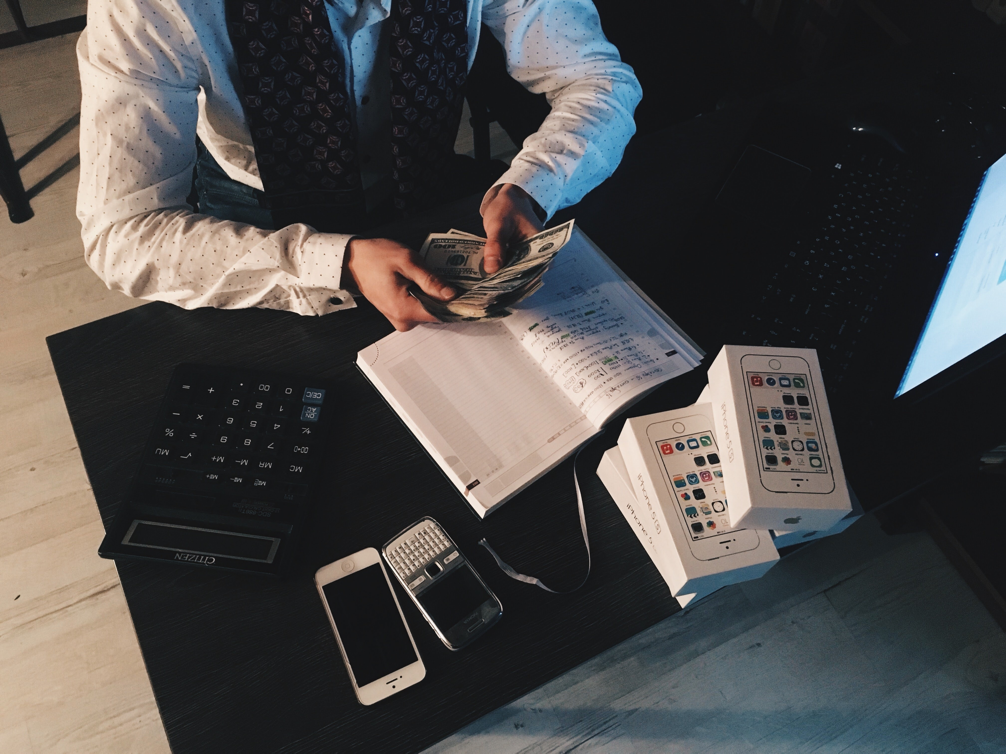 man sitting down counting money