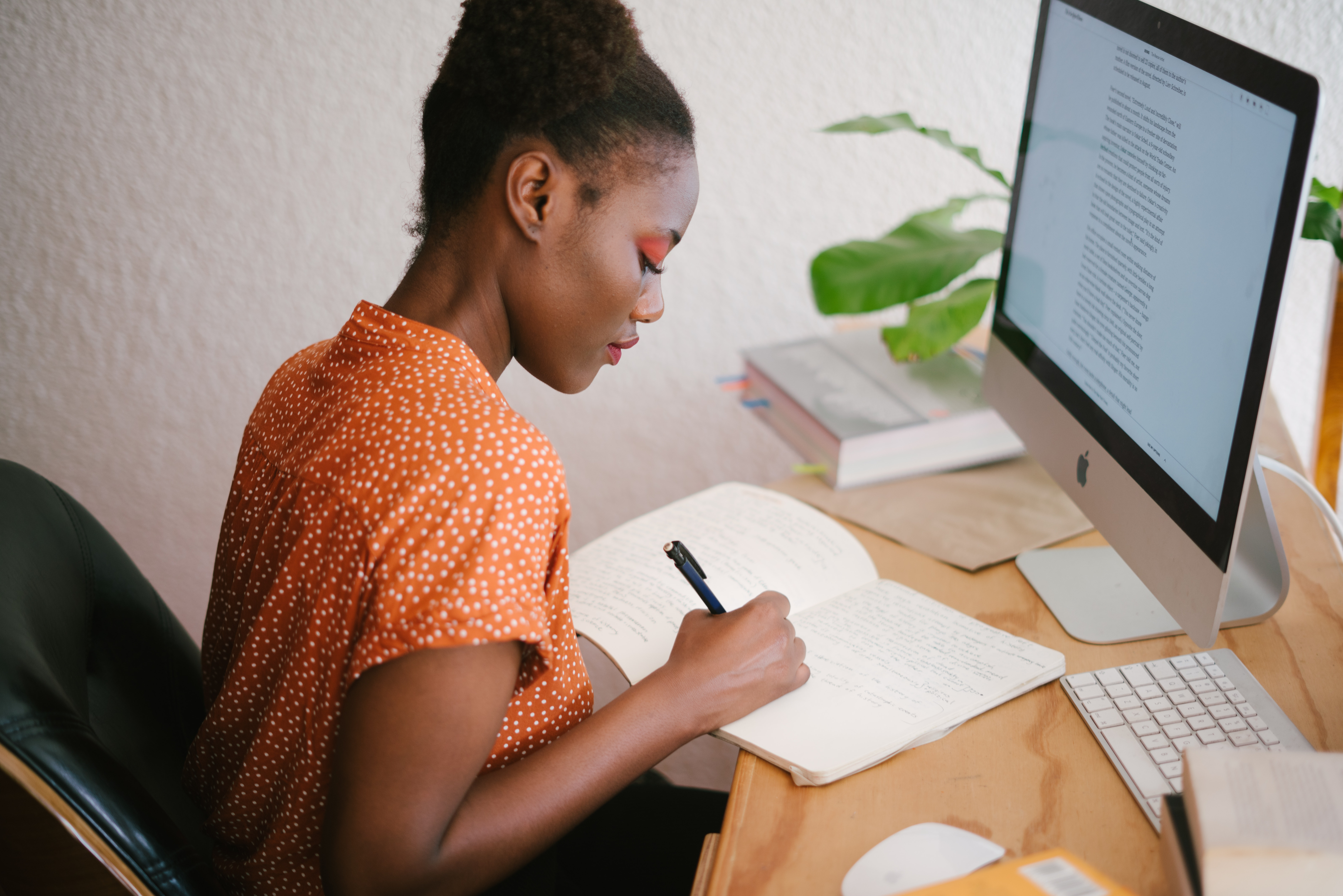 woman from dedicated team writing in notebook and working remotely