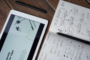 ipad notebook and pen on wooden table for data gathering
