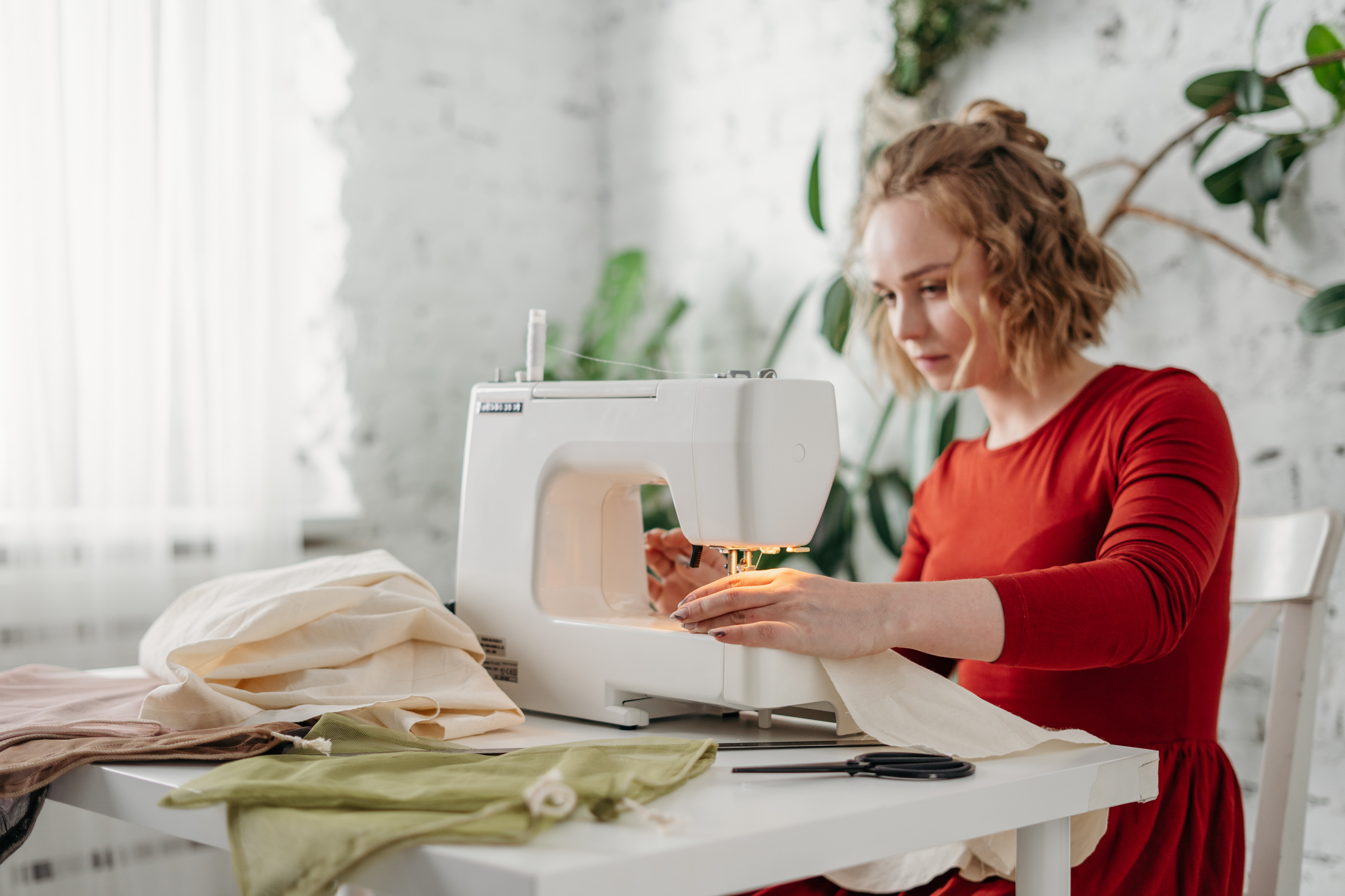 woman sewing handmade products for e-commerce business