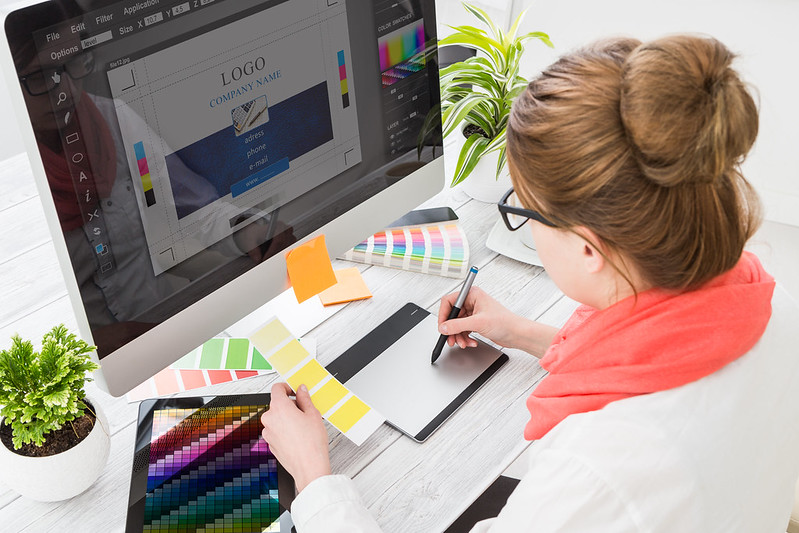 graphic designer using tablet and monitor to work on branding in art station