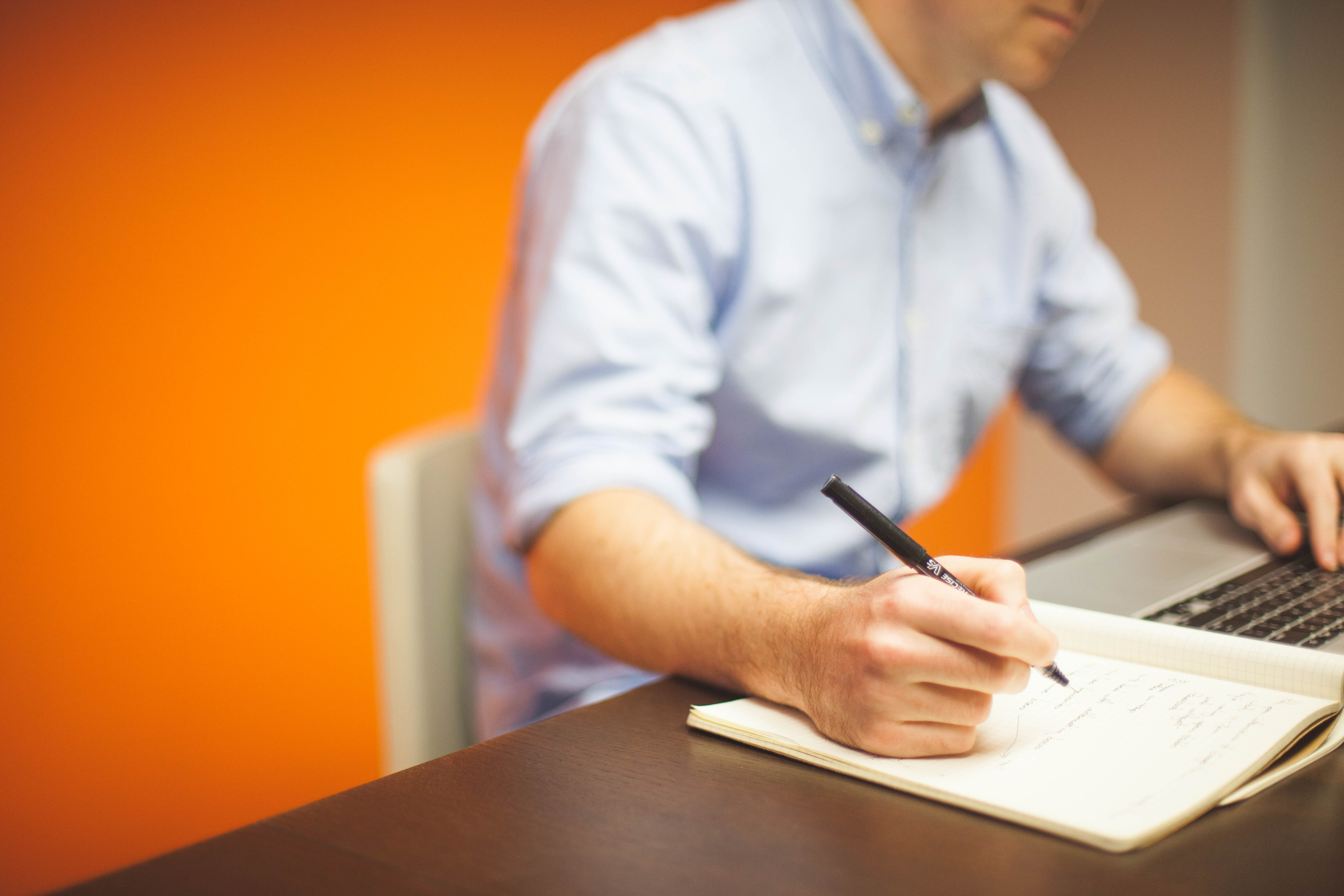 business man writing down details from personalized business email address